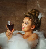 Girl is drinking wine in bath with foam. Royalty Free Stock Photos