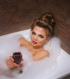 Girl is drinking wine in bath with foam. Stock Photos