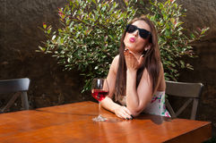 Girl drinking wine and blowing kiss on terrace Royalty Free Stock Photo