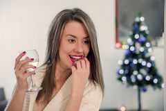 Girl drinking wine by the Christmas tree and thinking. Beautiful woman sitting next to Christmas tree enjoying glass of wine Royalty Free Stock Photography