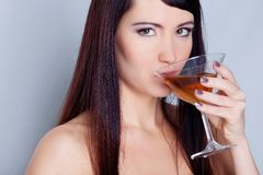 Girl drinking wine on grey background Royalty Free Stock Photo