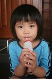 Girl drinking yogurt drink. Girl sitting on the floor drinking yogurt drinking Stock Photo