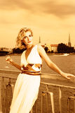 Girl drinks champagne. Beautiful blond girl drinks champagne near the river at sunset time Stock Photography
