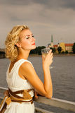 Girl drinks champagne. Beautiful blond girl drinks champagne near the rive Stock Photography