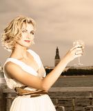 Girl drinks champagne. Beautiful blond girl drinks champagne near the river at sunset time Stock Photo
