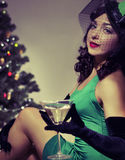 Girl drinks champagne retro. Woman sitting near a Christmas tree Stock Image