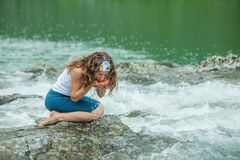 Girl drinks clear water from mountain river Stock Image