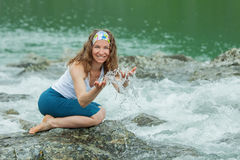 Girl drinks clear water from mountain river Royalty Free Stock Images