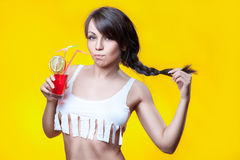 Girl drinks cocktail. Girl drinking cocktail on her short tank top, on a yellow background Stock Photo
