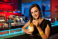 Girl drinks a cocktail in night club Stock Images
