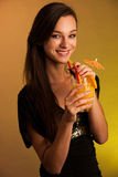 Girl drinks a cocktail in night club. Beautiful girl drinks a cocktail in night club Royalty Free Stock Photography