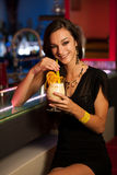 Girl drinks a cocktail in night club. Beautiful young woman drinks a cocktail Stock Photo