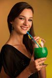 Girl drinks a cocktail in night club. Girl drinks a green cocktail in night club Stock Image