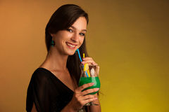 Girl drinks a cocktail in night club. Girl drinks a green cocktail in night club Royalty Free Stock Image