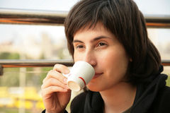 Girl drinks coffee. The young woman drinks coffee on street Royalty Free Stock Images