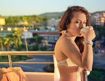 The girl drinks coffee on a balcony in underwear. The girl on a balcony drinks coffee Royalty Free Stock Photos