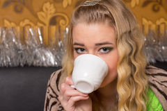 Girl drinks coffee from a mug. Covered with blanket Royalty Free Stock Images