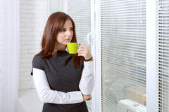 Girl drinks coffee near the window Stock Images