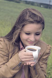 Girl drinks coffee with pleasure outdoors Royalty Free Stock Photo
