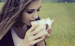 Girl drinks coffee with pleasure outdoors Royalty Free Stock Images