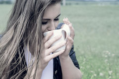 Girl drinks coffee with pleasure outdoors Stock Photo