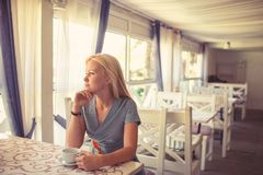 Girl drinks coffee or tea in cafe or restaurant. stock photography