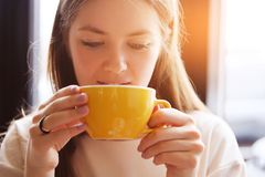 The girl drinks coffee from a yellow mug, looking down. Young beautiful woman sitting in a cafe, holding a Cup of cappuccino. royalty free stock image