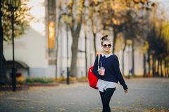 Pretty hipster teen with red bag drinks milkshake from a plastic cup walking street between buildings. Cute girl in royalty free stock photos