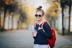 Pretty hipster teen with red bag drinks milkshake from a plastic cup walking street between buildings. Cute girl in royalty free stock image