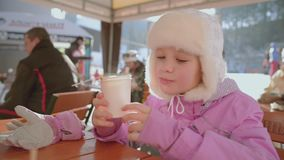 Girl Drinks Hot Tea or Cocktails at Cozy Snowy House Garden on Winter Morning. Beautiful Girl Enjoying Winter Outdoors with a Mug of Warm Drink. Christmas stock footage