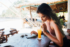 Girl drinks juice and checks the phone cafe on vacation with a view of the sea and the beach. Girl drinks juice and checks the phone in the hotel cafe on Royalty Free Stock Photo