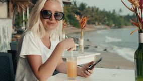 Girl drinks juice and checks the phone in the hotel cafe on vacation with a view of the sea and the beach. Portrait on a. Girl drinks juice and checks the phone stock video