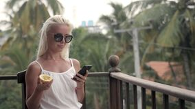 Girl drinks juice and checks the phone in the hotel cafe on vacation with a view of the sea and the beach with passion. Girl drinks juice and checks the phone in stock footage