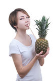Girl drinks juice from pineapple Stock Photo