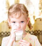 Girl drinks milk. Small beautiful girl drinks milk from a glass Royalty Free Stock Image