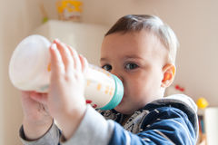 Girl drinks milk from a bottle Royalty Free Stock Image