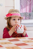 Girl drinks milk. From a cup Stock Photo