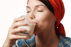 Girl drinks milk. Happy and young girl drinking milk with pleasure Royalty Free Stock Image