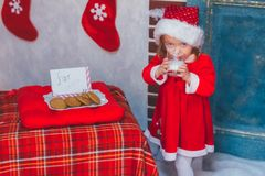 The girl drinks milk in the hat of Santa Claus. Beautiful little girl with milk and cookies for Santa Claus in festively decorated room Stock Photo