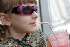 Girl drinks milk shake. The girl drinks strawberry milk shake in a cafe Royalty Free Stock Photography