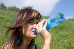 The girl drinks mineral water from a bottle Royalty Free Stock Image