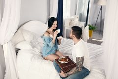 The girl drinks morning coffee, which her beloved husband brought to the bed. They are very happy stock photos