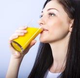 girl drinks natural orange juice Stock Images