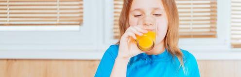 Girl drinks orange juice indoors Stock Photography