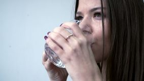 A girl drinks pills from a headache. Behind the light background stock footage
