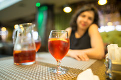 A girl drinks a red strawberry drink in a restaurant Royalty Free Stock Photos