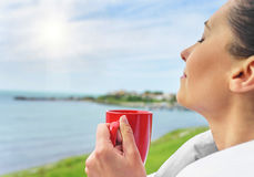Girl drinks tea on a background sea landscape. stock photography