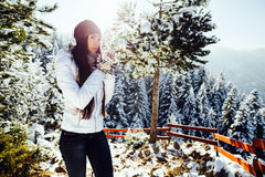 Girl drinks tea in cold winter forest with snow Stock Image