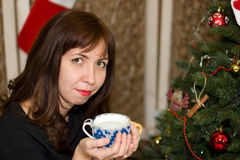 Girl drinks tea from a cup decorated christmas tree. Royalty Free Stock Photos