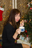 Girl drinks tea from a cup decorated christmas tree. Stock Images